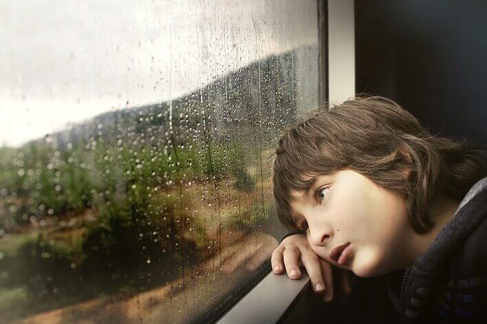 悩みながら窓の外を見る子供の写真